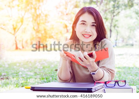 Asian young lady read book at outdoor in park. - stock photo