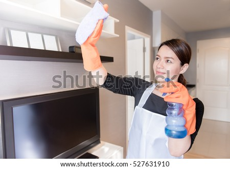 Asian young maid cleaning the mirror with spray at home, Cleaning service concept