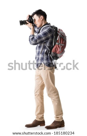 Asian young male backpacker take a picture, full length portrait isolated on white. - stock photo