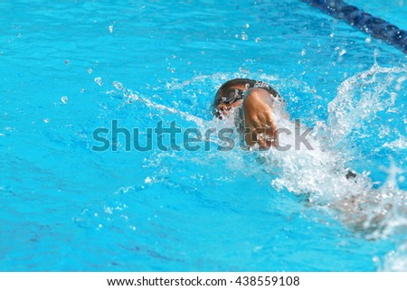 Asian young male swimmer practice forward crawl in a swimming pool for race, rear side view