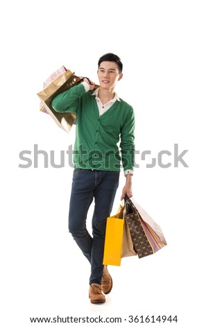 Asian young man holding shopping bags, full length portrait isolated. - stock photo