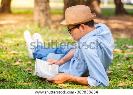 Asian young man reading a book on the grass in park - stock photo