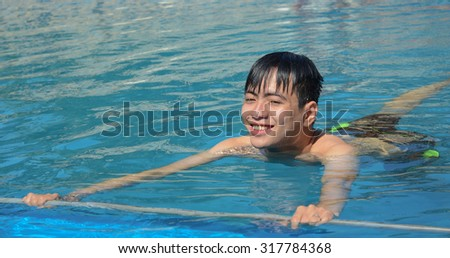 Asian young man relaxing on a swimming pool in Phan Thiet, Vietnam.