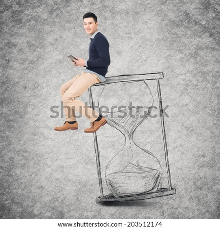 Asian young man sit on a hourglass and use tablet, concept of time management, technology, plan etc. - stock photo