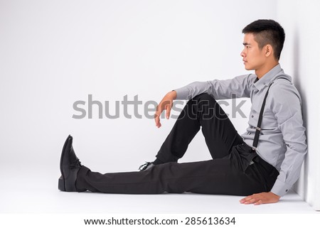 Asian young man sitting on floor and looking straight