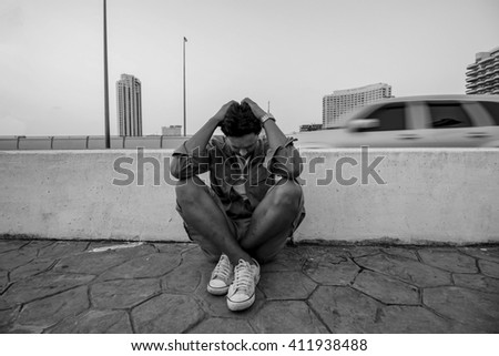 Asian young man with depression sitting beside street in a big city.