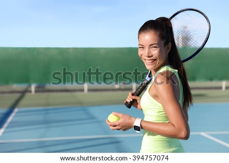 Asian young tennis player woman on outdoor summer court holding ball and racquet portrait. Female athlete wearing yellow sportswear and activity tracker smartwatch. wearable tech fitness watch.