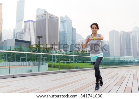 Asian Young Woman checking the data on sport watch while jogging - stock photo