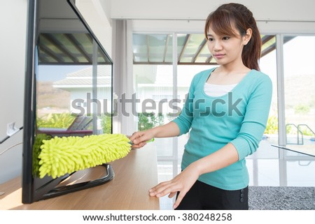 Asian young woman cleaning dust on TV at home  - stock photo