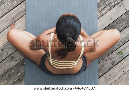 Asian young woman doing yoga on wooden floor