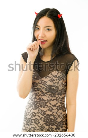 Asian young woman dressed up as a devil with finger in mouth isolated on white background - stock photo