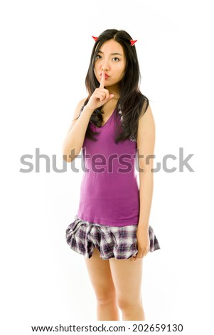 Asian young woman dressed up as a devil with finger on lips asking for silence isolated on white background - stock photo