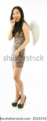 Asian young woman dressed up as an angel with finger in mouth isolated on white background - stock photo