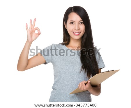 Asian Young Woman hold with file board and ok sign gesture - stock photo