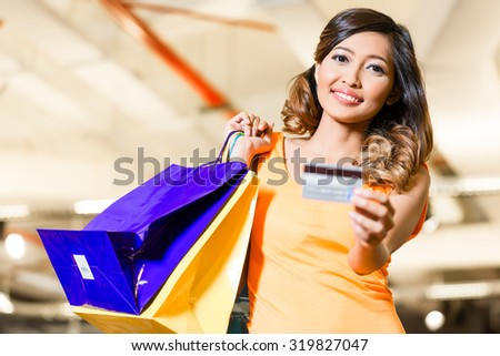 Asian young woman in fashion store or shop paying with credit card