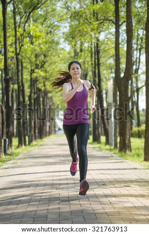 Asian young woman jogging in the forest, outdoors activity lifestyle