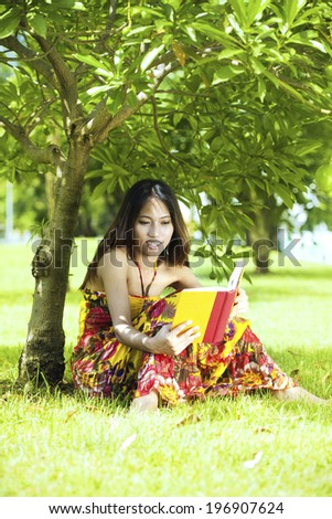 Asian young woman lying on the green grass and reading