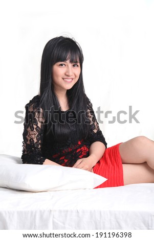 asian young woman sit on on bed smiling - stock photo