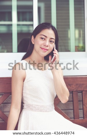 Asian young woman talking on mobile phone outside on home summer. Active lifestyle happy young adult on relaxing day at home. Vintage tone. - stock photo