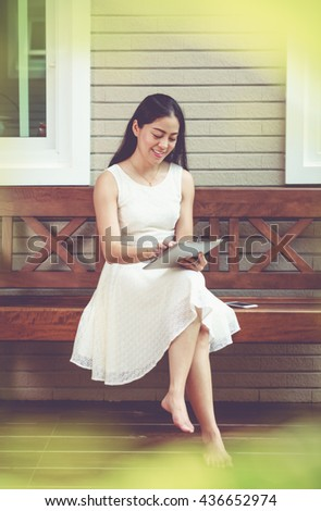Asian young woman using digital tablet outside on home summer. Active lifestyle happy young adult on relaxing day at home. Vintage tone. - stock photo