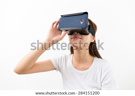 Asian young woman using virtual reality headset - stock photo