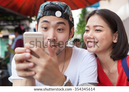 asian younger man and woman watching on smart phone with happy face - stock photo