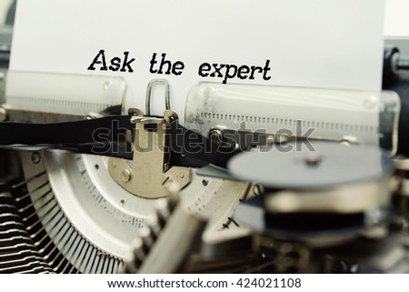 Ask the expert - Paper Sheets in Old Vintage Typewriter . Business concept on Toned, Grain Effect, Shallow Depth Of Field and Blurred Background - stock photo