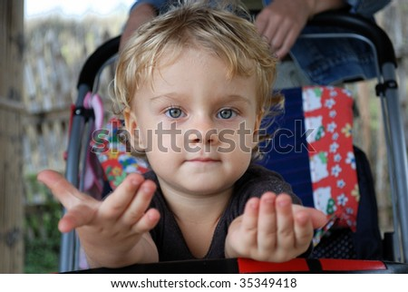 Asking little girl in a carriage - stock photo