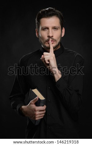 Asking to keep silence. Portrait of priest holding his hand against lips while standing against black background - stock photo
