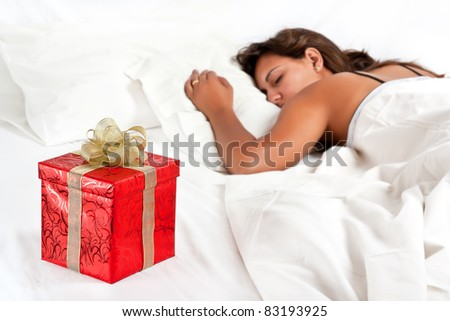 Asleep woman has a surprise present waiting for her in bed