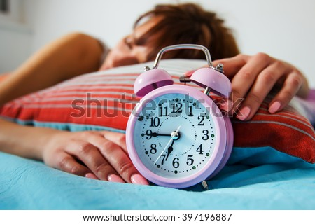 Asleep woman, turning off alarm clock, time for wake up.