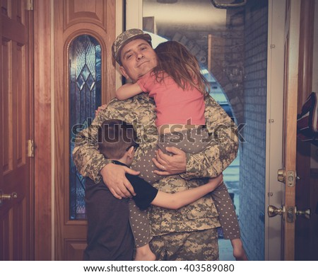 Asoldier man is coming home in the door and hugging his children for a love, family or reunited concept. - stock photo