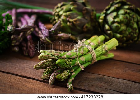 Asparagus and artichokes with herbs on a wooden background - stock photo