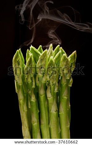 asparagus bunch with steam on black background - stock photo