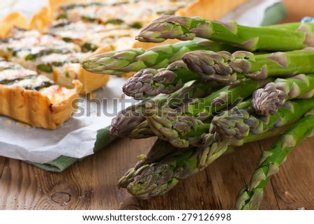 Asparagus for home made asparagus savory tart with pecorino and bacon on old wooden background.  Selective focus. - stock photo