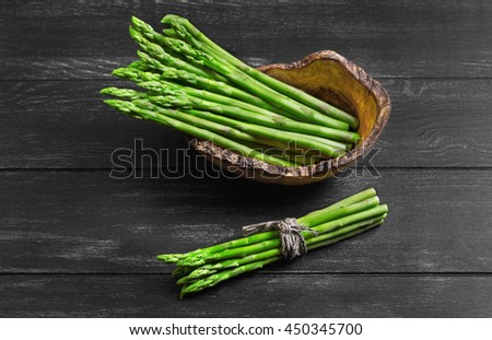 Asparagus green on dark black background wooden surface, asparagus beam tied with rope and twine in wooden bowl especially for asparagus, handmade from olive wood - stock photo