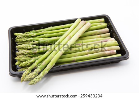 asparagus in black plastic tray on a white background. - stock photo