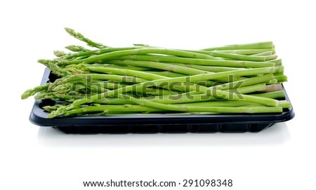 asparagus in black plastic tray on a white background - stock photo