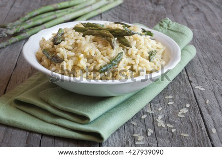 Asparagus risotto dish on wooden table - stock photo