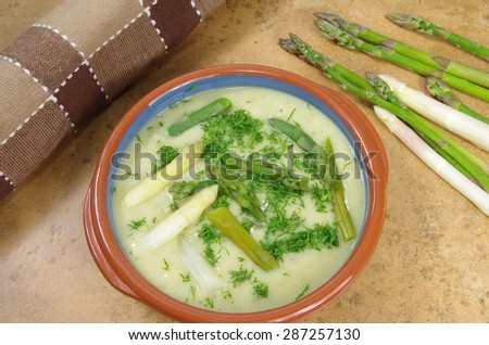 asparagus soup in plate on stone background - stock photo