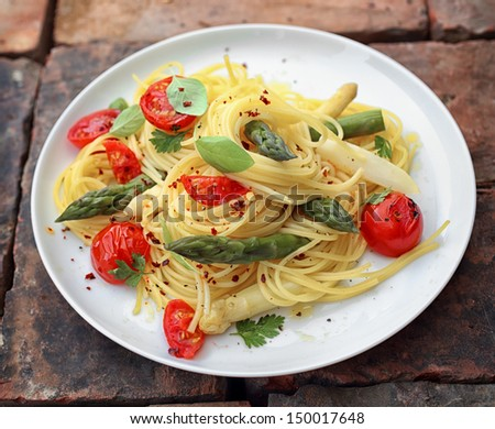 Asparagus spaghetti pasta with fresh green asparagus shoots, roasted cherry tomatoes and fresh basil seasoned with ground pepper - stock photo
