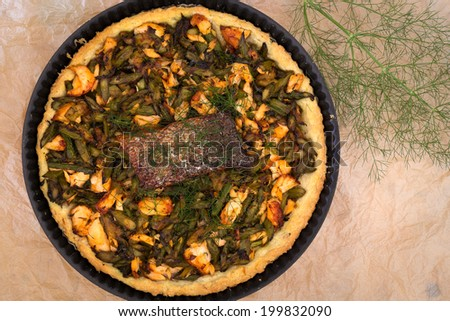 Asparagus zucchini salmon quiche with homemade shortcrust pastry and dill in backing tray with crispy salmon skin - stock photo