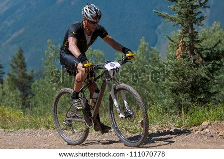 ASPEN, CO - AUG 25: Lance Armstrong climbing Aspen Mountain at the Power of Four mountain bike race in Aspen, CO on Aug 25, 2012 - stock photo