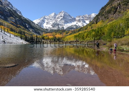Aspen, Colorado, USA - September 28, 2013: Tourists are enjoying a beautiful autumn day at Maroon Lake. After an overnight snow storm, the famous Maroon Bells look amazing with its fresh snow coating. - stock photo