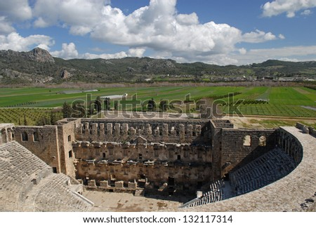 Aspendos is known for having the best-preserved theatre of antiquity. Bright green fields situated in the background flavor the ancient ruins. - stock photo