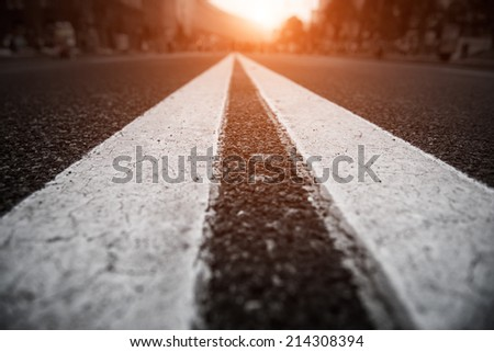 Asphalt city road with white lines ahead and the sunset - stock photo