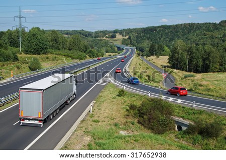 Asphalt highway with white truck and red passenger cars in wooded country. Electronic toll gate in the distance. View from above. Sunny summer day with blue skies.
