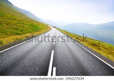 Asphalt road along the sea. Country houses. The Faroe Islands. - stock photo