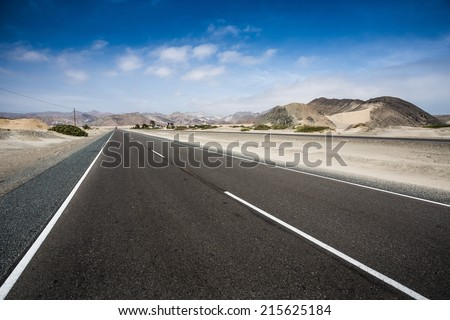 Asphalt road and blues sky trough  dessert - stock photo