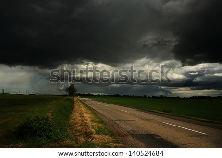 Asphalt road and dark storm clouds over it